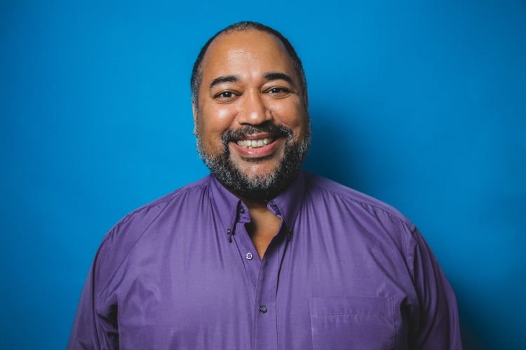Smiling profile image of Velvet Wells as The Velvet Duke on a gradient blue background. In the image, Velvet is a Black man smiling to the camera and wearing a purple dress shirt. Photo: Tyra Sweet (2019)
