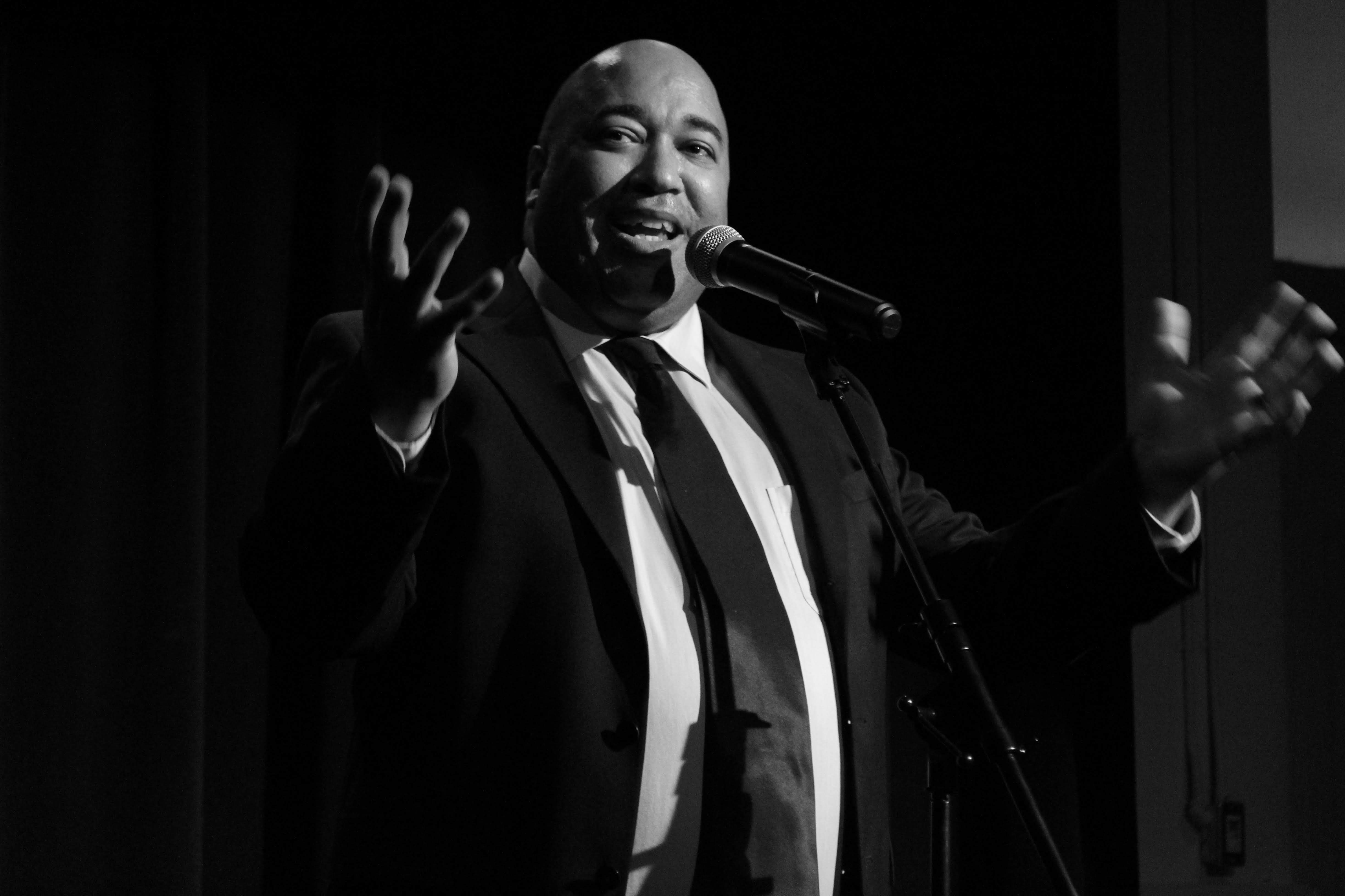 Grayscale image of Velvet Wells, a Black male in a black suit, speaking, into a microphone with a smile on his face. photo: Krissia Valiente