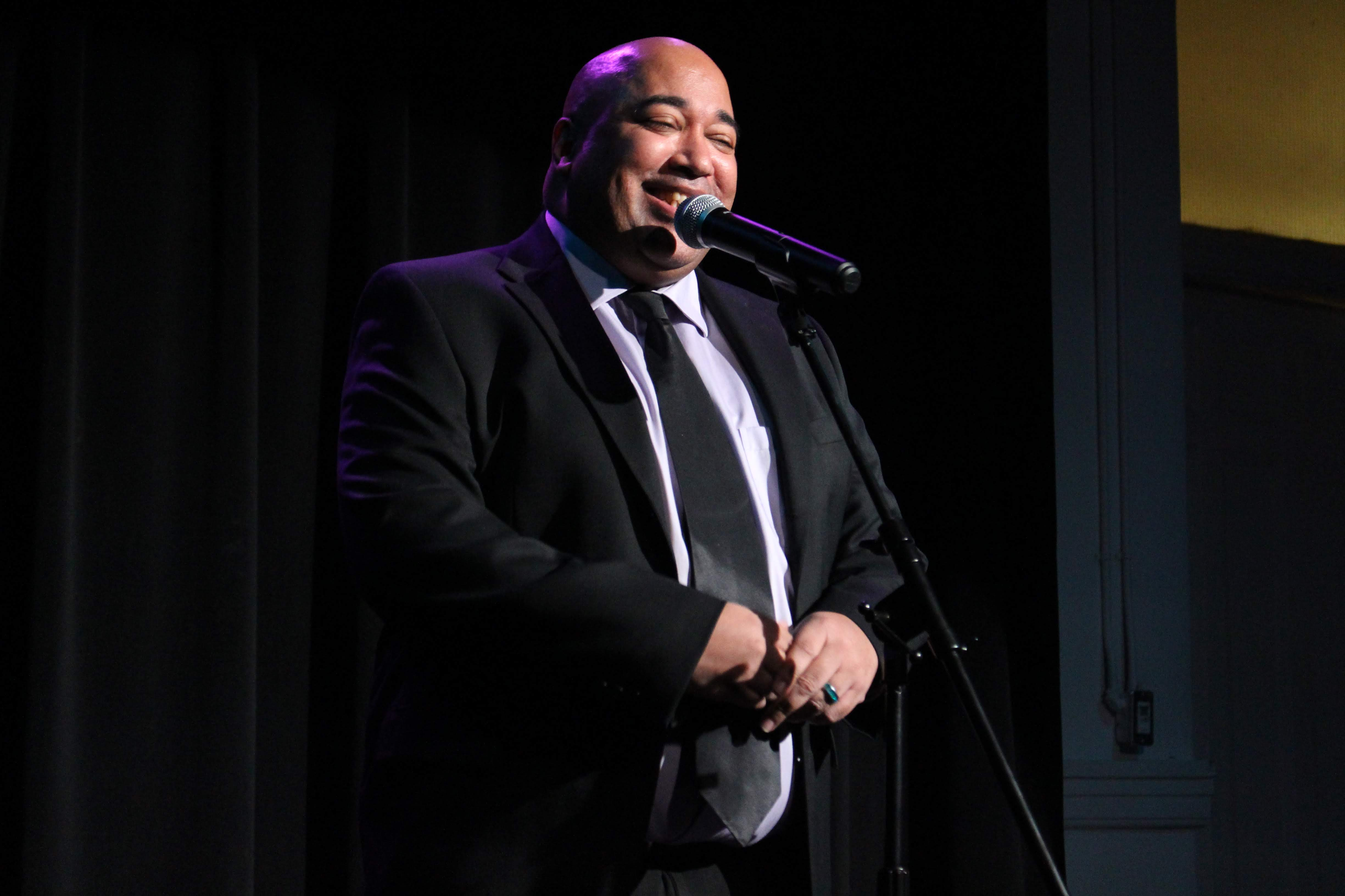 Velvet Wells Mirth photo: Krissia Valiente An image of Velvet Wells, a Black man in a black suit, smiling into a microphone. Black curtains are behind him, a purple light shines on his head and shoulders.